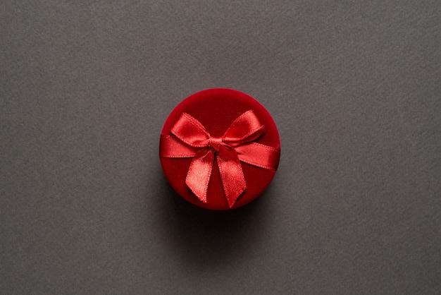 Caixa de jóias fechada vermelha redonda sobre um fundo preto