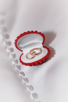 Caixa de jóias vermelha com alianças de casamento em tecido branco
