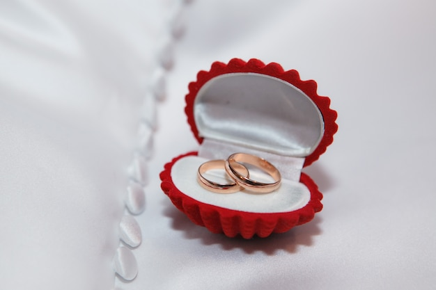 Caixa de jóias vermelha com alianças de ouro no tecido branco