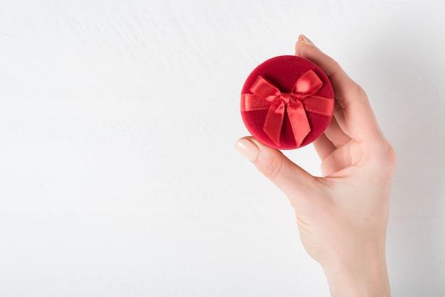 Caixa de jóias vermelha na mão feminina. presente. fundo branco
