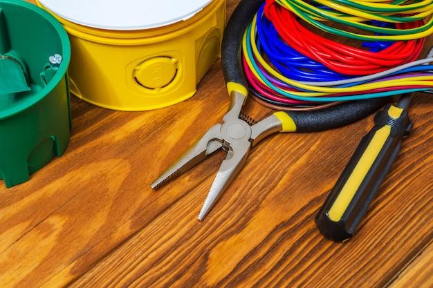 Caixa de junção elétrica com fios de cabos e ferramentas
