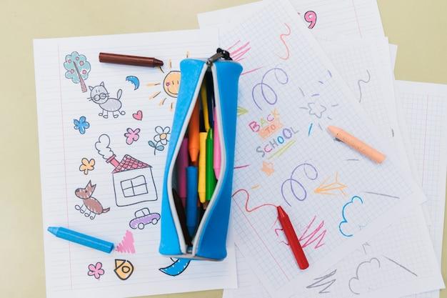 Caixa de lápis aberto e lápis de cera espalhados em desenhos de criança