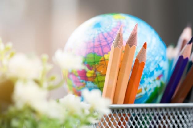 Caixa de lápis com o mapa da bola do modelo do globo da terra na cesta. conceito para negócios globais