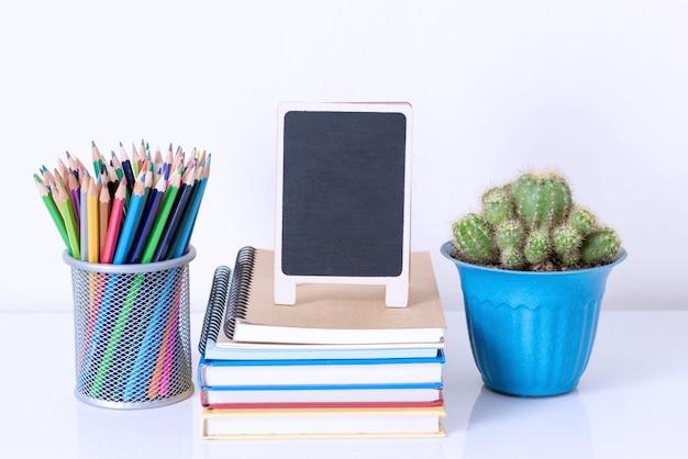 Caixa de lápis na pilha de livro e vaso de flores na mesa branca