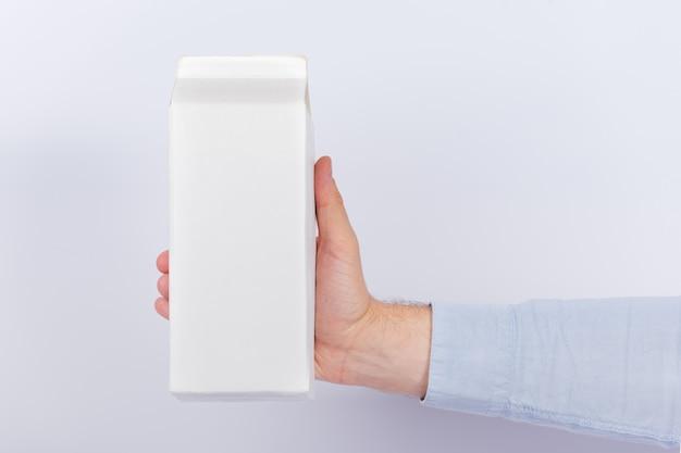 Caixa de leite ou suco na mão no fundo branco