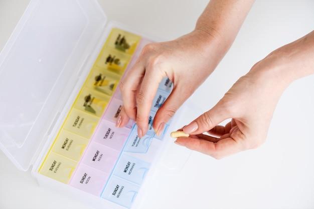 Caixa de lembrete de pílula diária em fundo branco