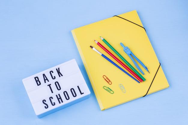 Caixa de luz com as palavras de volta à escola, um lápis, uma pasta, uma bússola e um pincel