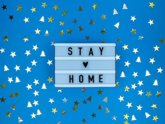 Caixa de luz com citação ficar em casa com confete. quarentena de natal.