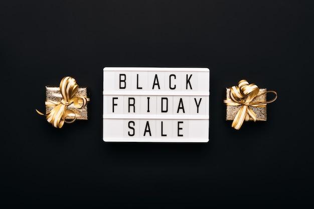 Caixa de luz com o texto venda de sexta-feira preta e caixas de presente douradas sobre fundo preto.