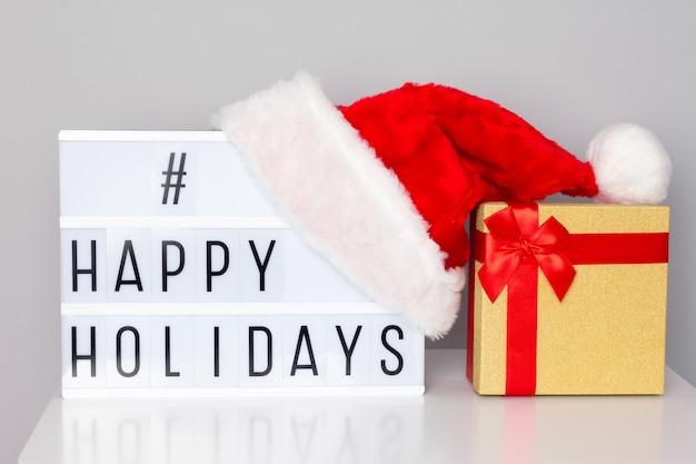 Caixa de luz com texto hashtag de boas festas, chapéu de papai noel e caixa de presente na mesa branca