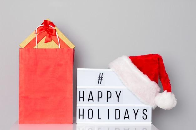Caixa de luz com texto hashtag de boas festas usando chapéu de papai noel e sacola de compras com presentes de natal