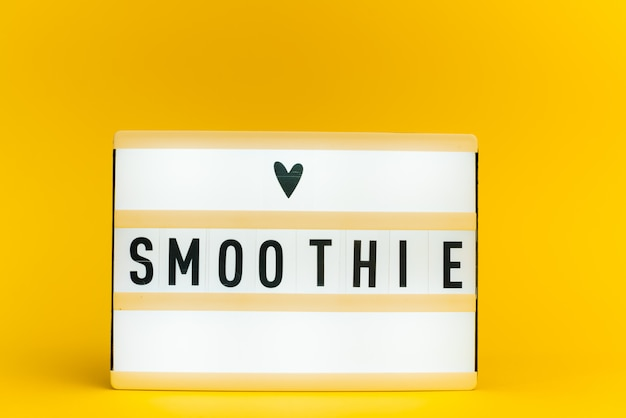 Caixa de luz com texto, smoothie, na parede amarela