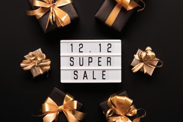 Caixa de luz com texto super venda e caixas de presente douradas sobre fundo preto. composição de promoção plana de 12 mega dias de vendas duplo.