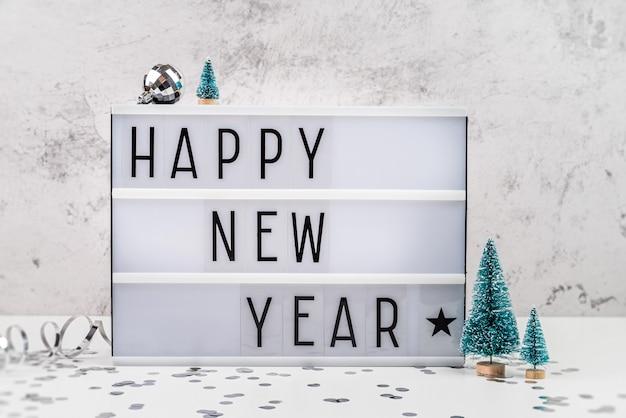 Caixa de luz de letra branca com feliz ano novo, com vista frontal para decorações de natal