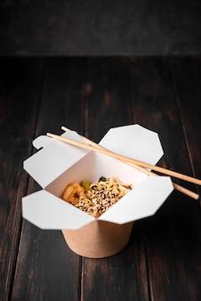 Caixa de macarrão com sementes de gergelim e pauzinhos