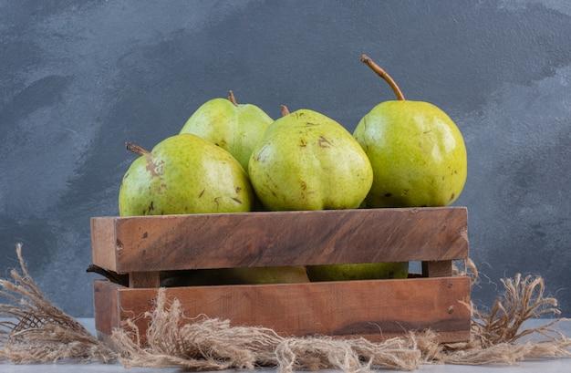 Caixa de maçãs verdes maduras orgânicas frescas na mesa de madeira.