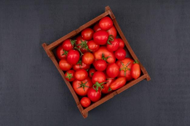 Caixa de madeira cheia com tomates frescos brilhantes vermelhos na vista superior de superfície preta