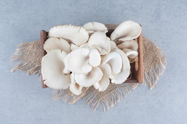 Caixa de madeira cheia de cogumelos ostra no saco.