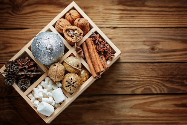 Caixa de madeira cheia de decorações de natal, bola, guizos, nozes, cones, canela, marshmallow