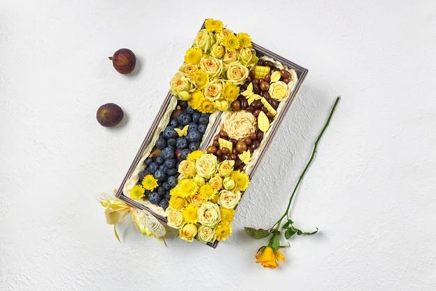 Caixa de madeira cheia de flores amarelas, mirtilos e chocolate