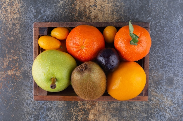 Caixa de madeira cheia de frutas frescas na mesa de mármore.