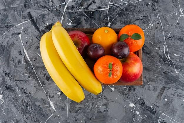 Caixa de madeira cheia de frutas frescas na superfície de mármore.