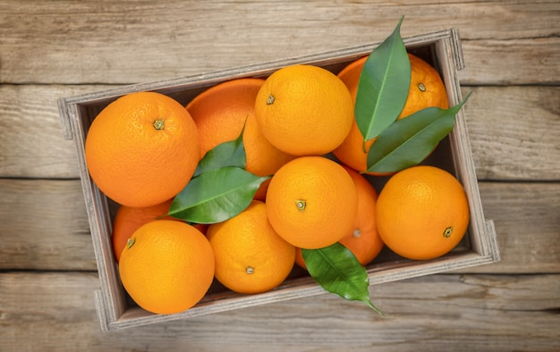 Caixa de madeira cheia de laranjas na vista superior do plano de fundo de madeira