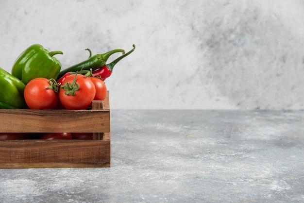Caixa de madeira cheia de legumes frescos em mármore.