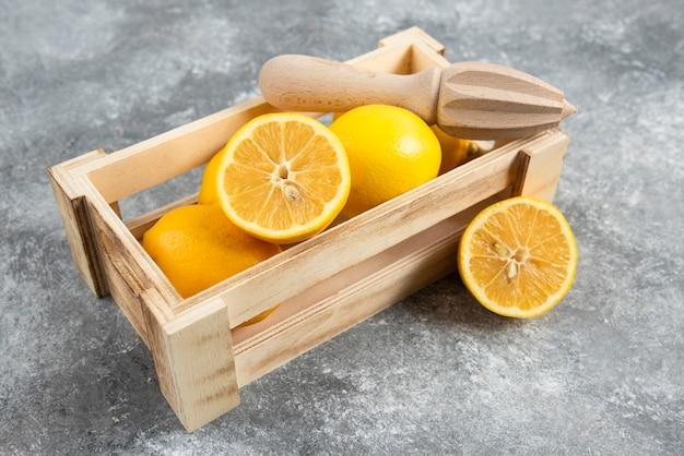 Caixa de madeira cheia de limões frescos com espremedor de limão.