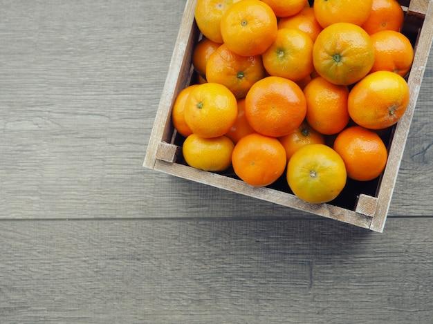 Caixa de madeira cheia de tangerinas. uma tangerina descascada