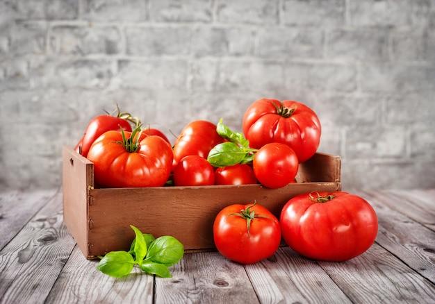 Caixa de madeira cheia de tomates colhidos maduros, vermelhos e suculentos.