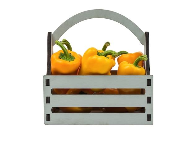 Caixa de madeira cinza com pimenta laranja isolada em um fundo branco. comida vegetariana.