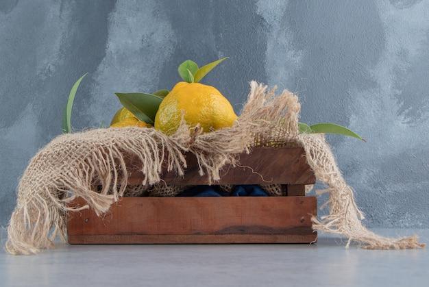 Caixa de madeira coberta com um pedaço de pano, cheia de tangerinas sobre mármore.