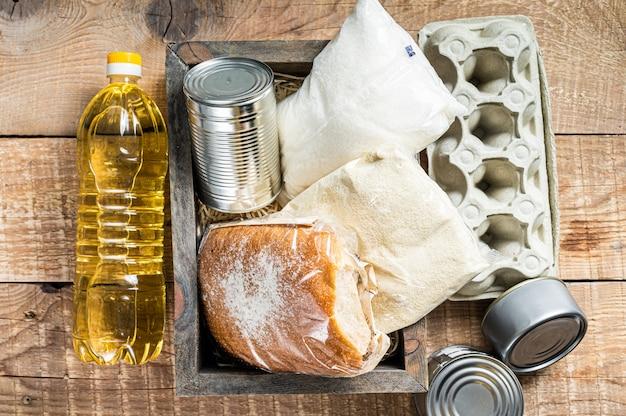 Caixa de madeira com comida de doação, conceito de ajuda de quarentena. óleo, comida enlatada, macarrão, pão, açúcar, ovo. fundo de madeira. vista do topo.