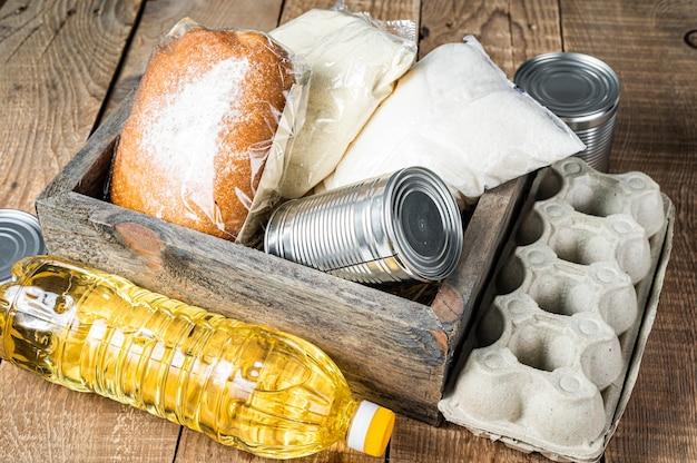 Caixa de madeira com comida de doação, conceito de ajuda de quarentena. óleo, comida enlatada, macarrão, pão, açúcar, ovo
