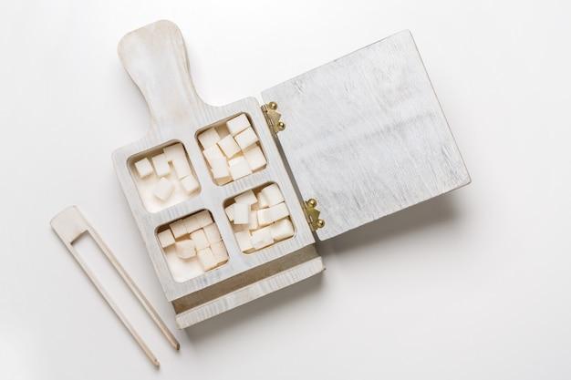 Caixa de madeira com cubos de açúcar branco e pinças na mesa, vista superior