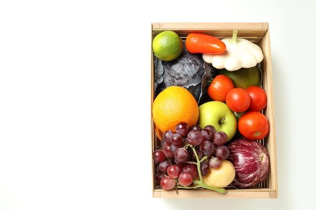 Caixa de madeira com legumes e frutas em fundo branco