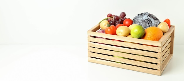 Caixa de madeira com legumes e frutas na mesa branca