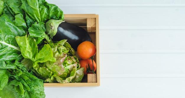 Caixa de madeira com legumes em uma mesa de madeira branca.