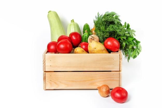 Caixa de madeira com legumes em uma parede branca. abobrinha, cenoura, tomate, pepino e verduras. produtos agrícolas. vegetais frescos.