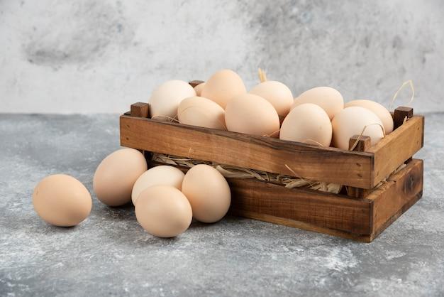 Caixa de madeira com ovos crus orgânicos na superfície de mármore.
