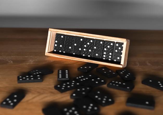 Caixa de madeira com peças de dominó e dados espalhados sobre mesa de madeira