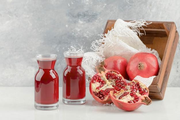 Caixa de madeira com romãs vermelhas frescas e suco delicioso na mesa branca.