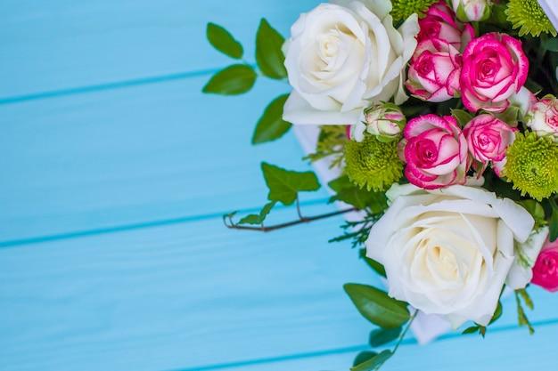 Caixa de madeira com rosas brancas e rosa e crisântemos na placa de madeira turquesa. decoração de casa. caixas de flores. decoração de casamento