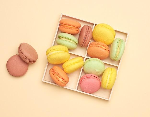 Caixa de madeira e biscoitos macarons multicoloridos assados em um bege