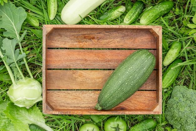 Caixa de madeira e vegetais verdes na grama conceito saudável comer colheita