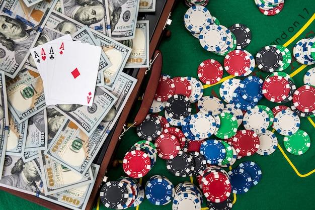 Caixa de madeira para fichas de pôquer com cartas de jogar e dólares americanos na mesa verde