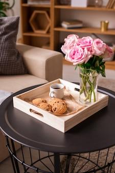 Caixa de madeira quadrada com buquê de rosas frescas em vidro, xícara de café e biscoitos em uma pequena mesa redonda em ambiente doméstico
