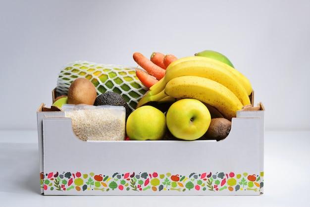 Caixa de mantimentos com legumes e frutas no fundo branco da cozinha