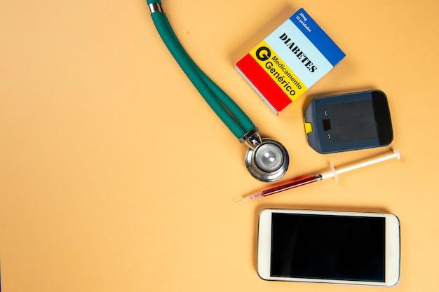 Caixa de medicamentos com o nome da doença diabetes e glicosímetro
